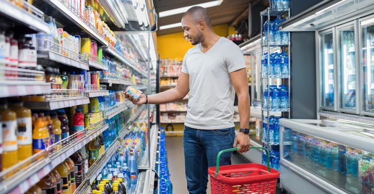Supermarket shopper examines product from shelf