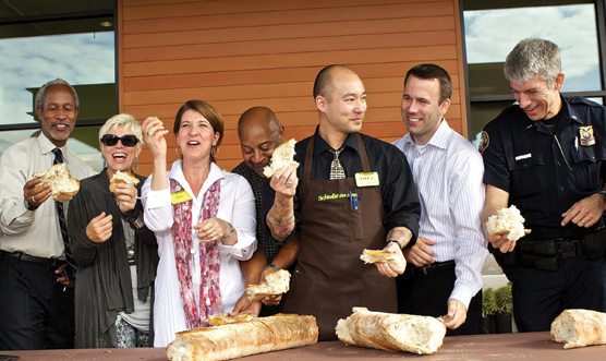 New Seasons CEO Wendy Collie (third from left) joins store staff and local community leaders at a 'bread-breaking' celebrating the chain's newest store opening  in Portland, Ore.