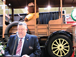 A 1926 Ford Model T serves as a backdrop as Christopher Kinsley Sr. speaks at the grand opening event.